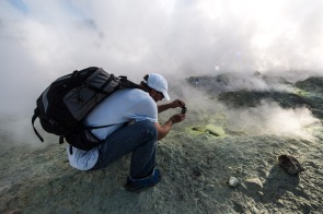 Philippe photographiant les gazs d'une fumerolle en haut du grand cratère de Vulcano, photo Serge Briez, Cap médiations 2014